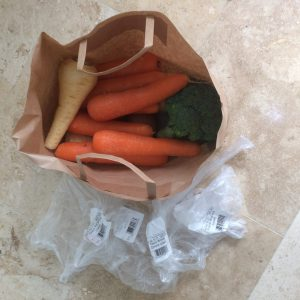 Paper bag with carrots, parsnips and broccoli and the plastic bags that were added