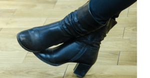 Women's feet with black ankle chunky heeled boots