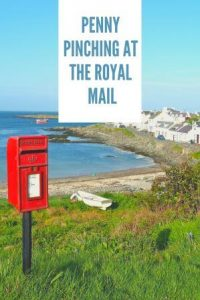 old fashioned post box on stick on cliff top background sea