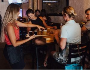 3 women round table being served drinks