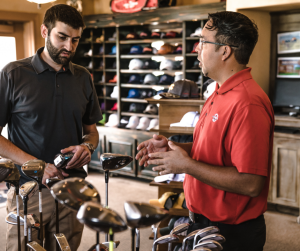 man and sales assistant talking over golf clubs