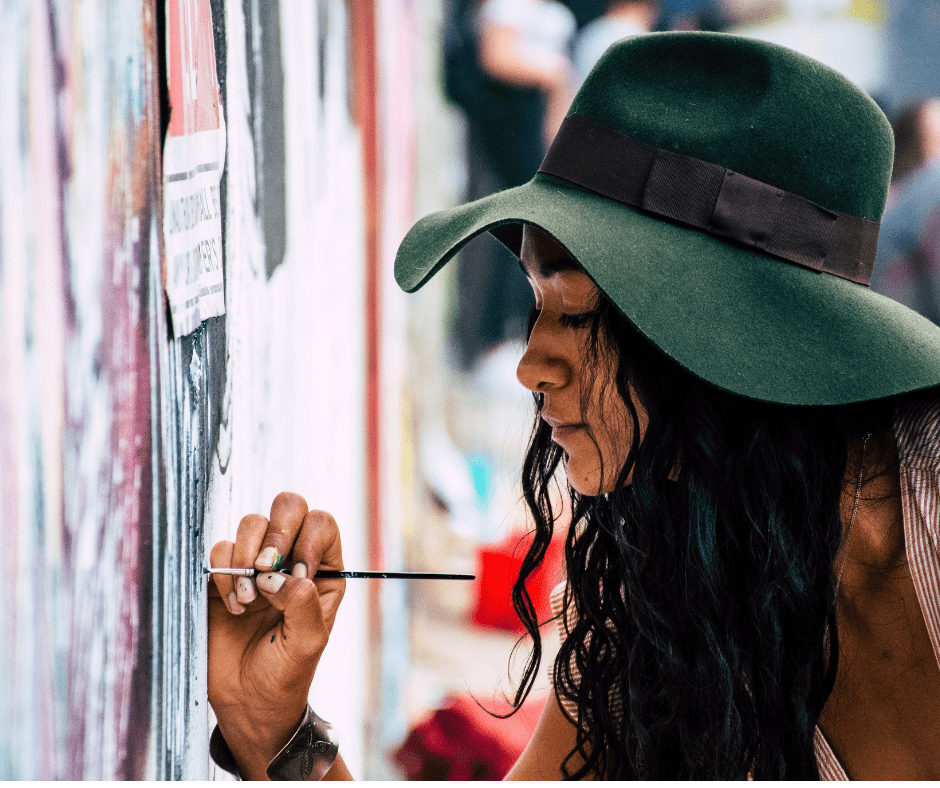 Woman in hat painting on a wall